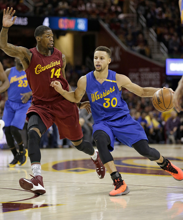 . Golden State Warriors\' Stephen Curry (30) drives past Cleveland Cavaliers\' DeAndre Liggins (14) in the second half of an NBA basketball game, Sunday, Dec. 25, 2016, in Cleveland. (AP Photo/Tony Dejak)