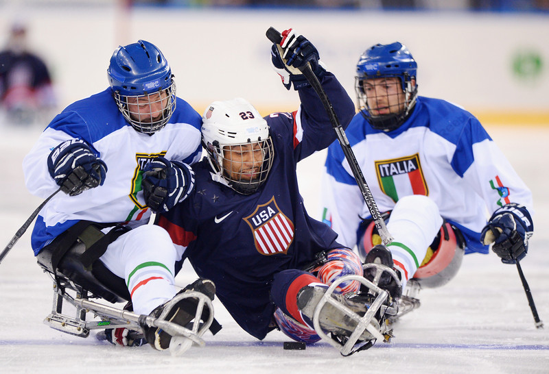 . Valerio Corvino of Italy challenges Rico Roman of the United States during the Ice Sledge Hockey Preliminary Round Group A match between the United States of America and Italy at Shayba Arena on March 8, 2014 in Sochi, Russia.  (Photo by Dennis Grombkowski/Getty Images)