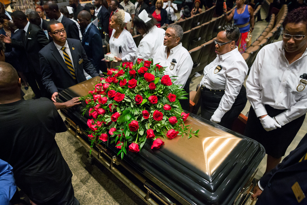 Description of . A casket containing the body of Michael Brown is wheeled out Monday, Aug. 25, 2014, at Friendly Temple Missionary Baptist Church in St. Louis. Hundreds of people gathered to say goodbye to Brown, who was shot and killed by a Ferguson, Mo., police officer on Aug. 9. (AP Photo/New York Times, Richard Perry, Pool)