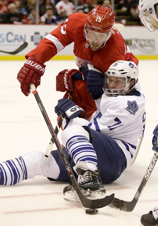 . Detroit Red Wings\' Riley Sheahan (15) knocks the puck away from Toronto Maple Leafs\' David Clarkson during the second period of an NHL hockey games Saturday, Oct. 18, 2014, in Detroit. (AP Photo/Duane Burleson)