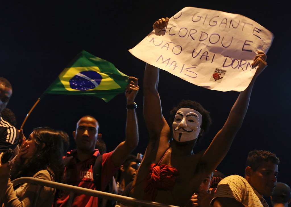 """. A protester wearing a Guy Fawkes mask holds a sign during a protest outside Rio de Janeiro governor Sergio Cabral\'s house, in Rio de Janeiro June 21, 2013.  The sign reads,  \""""The giant awakens and he will sleep no more\"""". REUTERS/Pilar Olivares"""