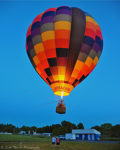 A tethered hot air balloon pilot uses a burner to lift passengers over the Oswego Country Fairgrounds during the Oswego Balloonfest in Sandy Creek, New York.