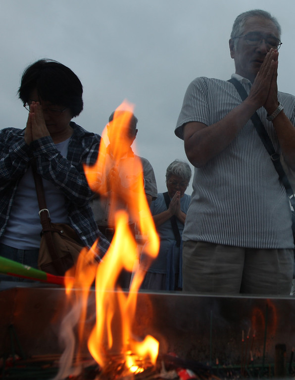 . People pray in front of a monument for atomic bomb victims at the Hiroshima Peace Memorial Park on the day of the 68th anniversary of the atomic bombing of Hiroshima on August 6, 2013 in Hiroshima, Japan.   (Photo by Buddhika Weerasinghe/Getty Images)