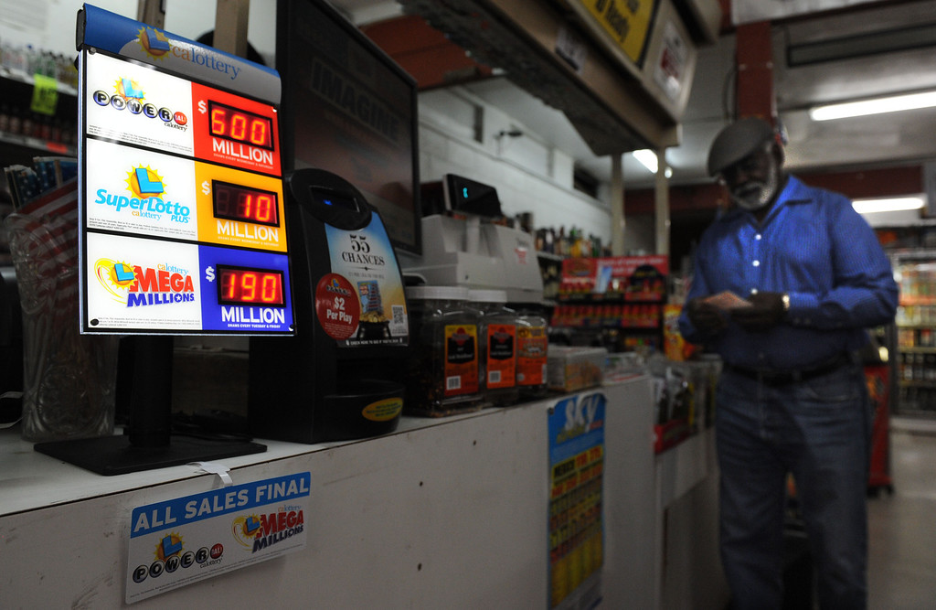 """. (John Valenzuela/Staff Photographer)  Adolphus Fulcher of San Bernardino looks over is Powerball numbers at Brookside Market in Redlands, Fulcher said \""""If I won the jackpot I would buy a jet and take trip around the world\"""", Saturday\'s jackpot is over 600 million, third largest in Powerball history."""