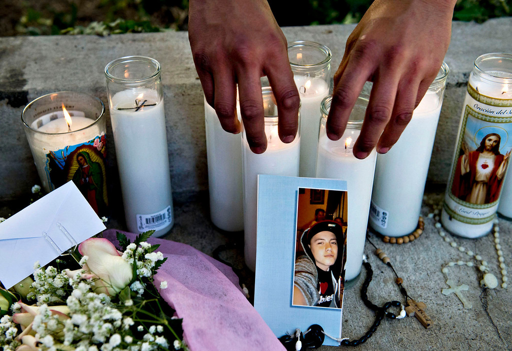 . Carlos Davila, 16, of Azusa, places candles at a makeshift memorial for his friend Cristopher Rossi, 16, outside his apartment in 2500 block of Huntington Drive in Duarte on Tuesday, Dec. 24, 2013. Rossi was fatally shot outside his home Monday night. (Staff photo by Watchara Phomicinda/ San Gabriel Valley Tribune)