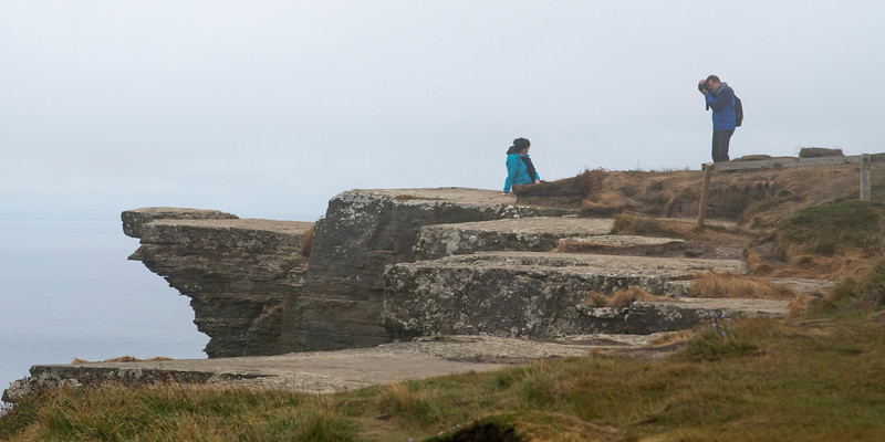 Man photographing his wife on the cliff, Cliffs of Moher, Ennistymon, County Clare, Ireland