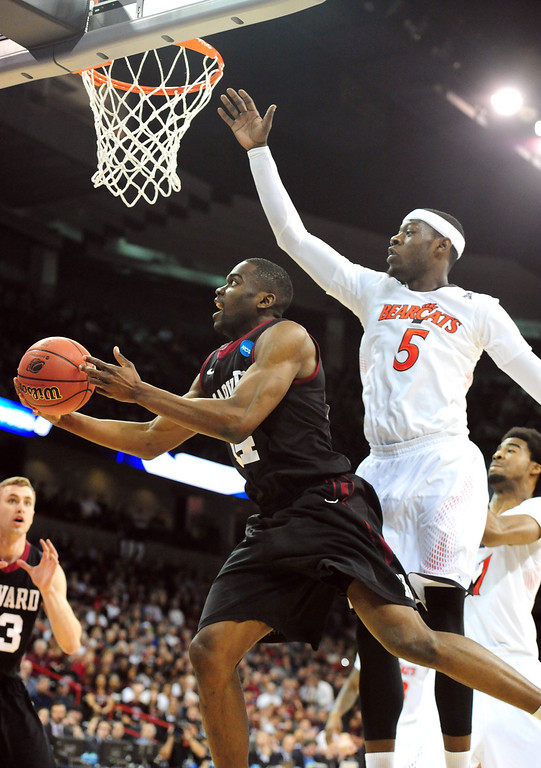 . Steve Moundou-Missi #14 of the Harvard Crimson goes up for a shot against Justin Jackson #5 of the Cincinnati Bearcats during the second round of the 2014 NCAA Men\'s Basketball Tournament at Spokane Veterans Memorial Arena on March 20, 2014 in Spokane, Washington.  (Photo by Steve Dykes/Getty Images)