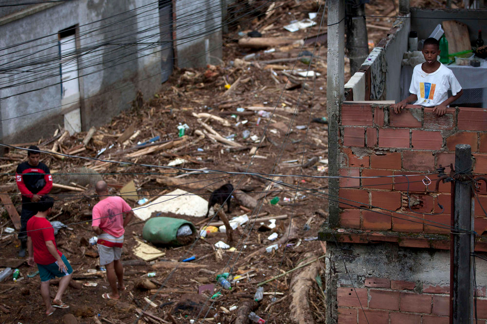 Description of . Residents look at debris left by a flood caused by heavy rains in the Xerem neighborhood, about 31 miles north of Rio de Janeiro, Brazil, Thursday, Jan. 3, 2013. Nearly 8.5 inches of rain fell in just 24 hours in the mountainous region north of Rio. Hard rains in Brazil are creating a state of alert in Rio de Janeiro and in nearby spots where flood-triggered mudslides have killed hundreds in recent years.  (AP Photo/Felipe Dana)