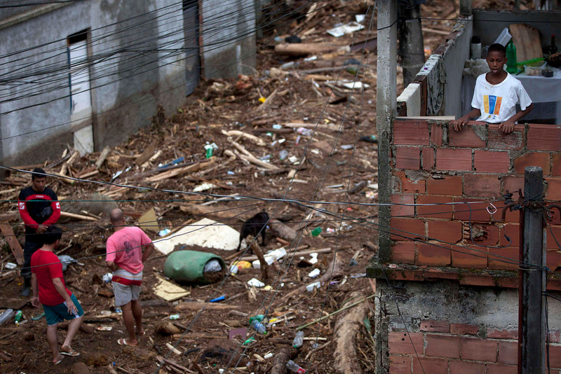 . Residents look at debris left by a flood caused by heavy rains in the Xerem neighborhood, about 31 miles north of Rio de Janeiro, Brazil, Thursday, Jan. 3, 2013. Nearly 8.5 inches of rain fell in just 24 hours in the mountainous region north of Rio. Hard rains in Brazil are creating a state of alert in Rio de Janeiro and in nearby spots where flood-triggered mudslides have killed hundreds in recent years.  (AP Photo/Felipe Dana)