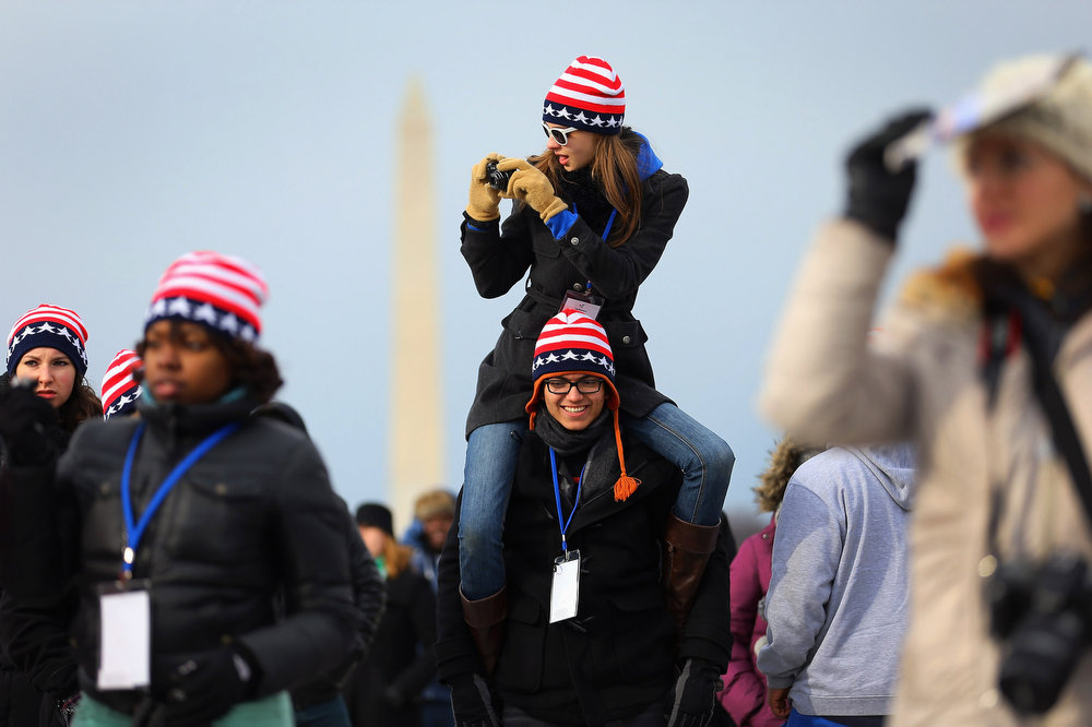 . Sydney Yochum sits on the shoulders of Luis Lauro Lopez near the U.S. Capitol building on the National Mall as they and others wait for the start of the Inauguration ceremony on January 21, 2013 in Washington, DC.  U.S. President Barack Obama will be ceremonially sworn in for his second term today.  (Photo by Joe Raedle/Getty Images)