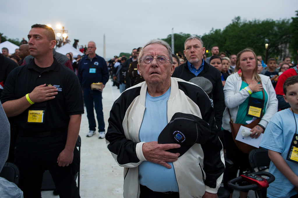 . Family members of police officers killed in the line of duty cover their hearts during the singing of the National Anthem at the start of the National Law Enforcement Officers Memorial Fund 30th annual Candlelight Vigil, to commemorate new names added to the monument, on the Mall in Washington, Sunday, May 13, 2018. (AP Photo/Cliff Owen)