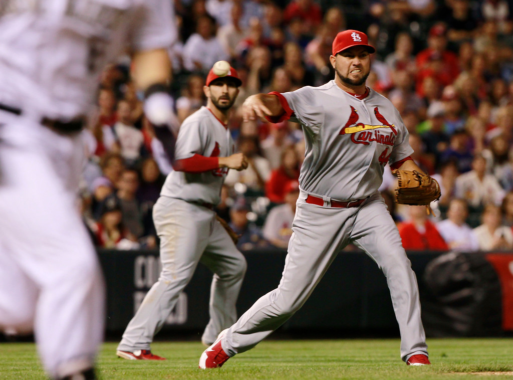 . St. Louis Cardinals relief pitcher Edward Mujica, back, throws to first base after fielding a sacrifice bunt to put out Colorado Rockies\' Corey Dickerson, front, as third baseman Daniel Descalso watches during the ninth inning of the Cardinals\' 4-3 victory in a baseball game in Denver on Wednesday, Sept. 18, 2013. (AP Photo/David Zalubowski)