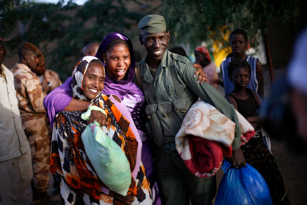 . Malian women pose with a Malian soldier who just arrived in a convoy at the military base in Timbuktu, Mali, Saturday Feb. 2, 2013. French President Francois Hollande visited the fabled city for two hours, twenty days after the start of operation Serval. (AP Photo/Jerome Delay)