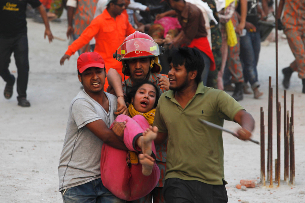 . Rescue workers carry a garment worker who was trapped inside the rubble of the Rana Plaza building which collapsed, in Savar, 30 km (19 miles) outside Dhaka April 24, 2013. REUTERS/Andrew Biraj