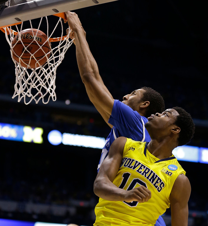 . Kentucky\'s Marcus Lee (00) dunks against Michigan\'s Derrick Walton Jr. (10) during the first half of an NCAA Midwest Regional final college basketball tournament game Sunday, March 30, 2014, in Indianapolis. (AP Photo/Michael Conroy)