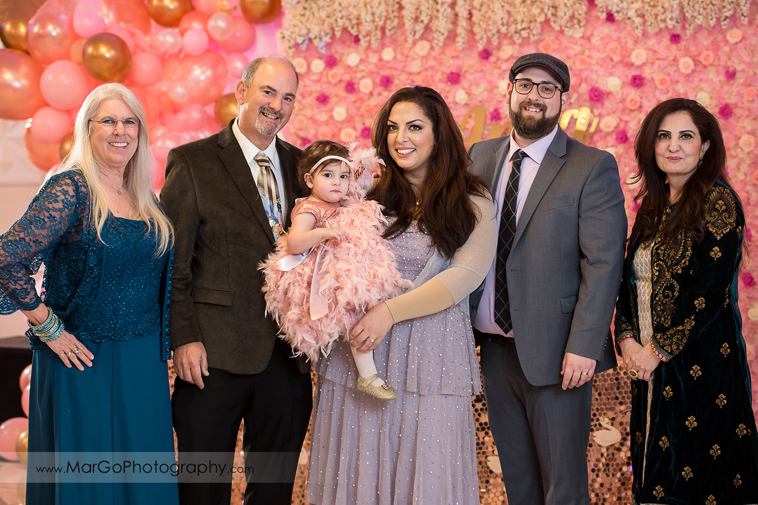 family portrait on pink and white roses wall at Newark Oasis Palace