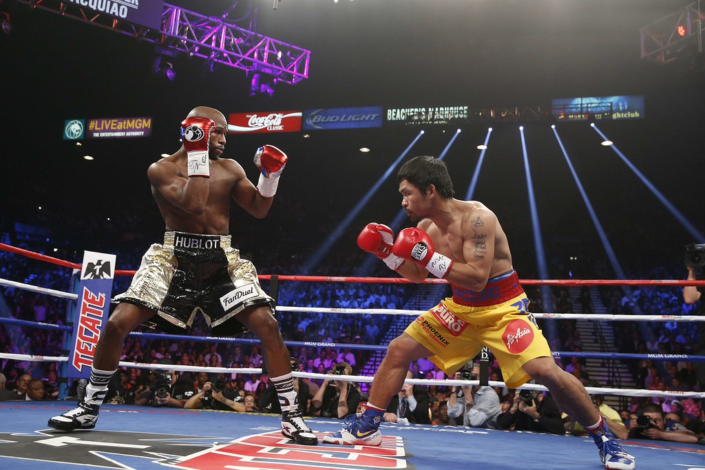 . Floyd Mayweather Jr., and Manny Pacquiao (R) fight in a welterweight unification bout on May 2, 2015 at the MGM Grand Garden Arena in Las Vegas, Nevada. AFP PHOTO / JOHN GURZINKSIJOHN GURZINSKI/AFP/Getty Images