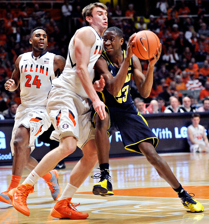 . Michigan guard Caris LeVert (23) collides with Illinois forward Jon Ekey (33) on a drive during the second half in an NCAA college basketball game Tuesday, March 4, 2014, in Champaign, Ill. Michigan won 84-53. (AP Photo/Rick Danzl)