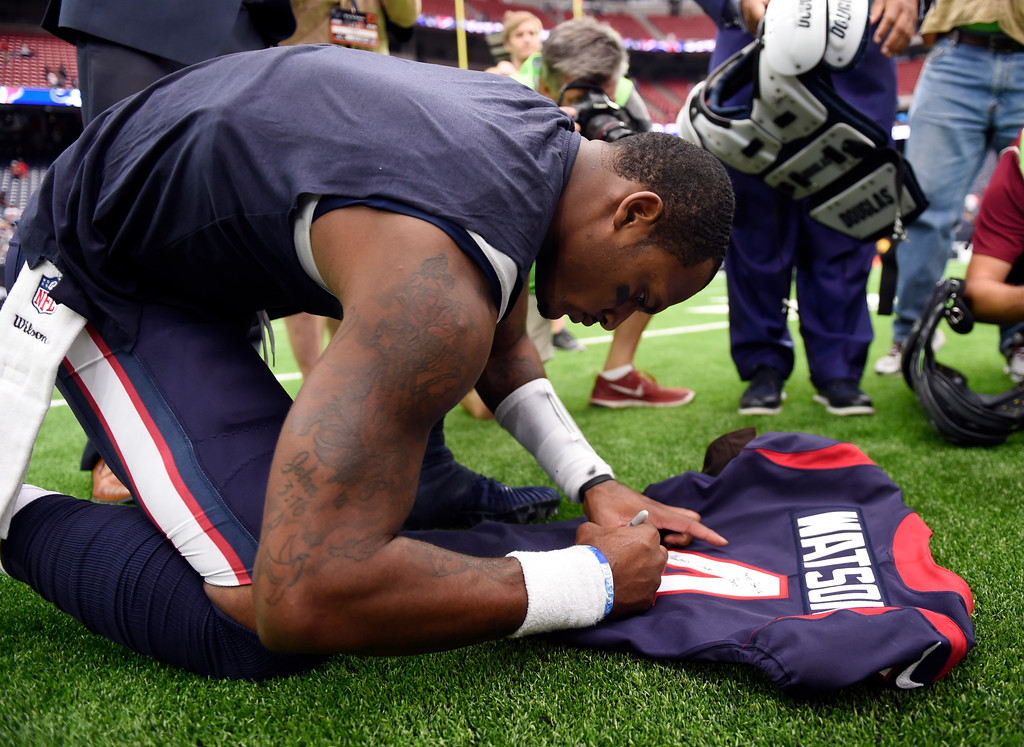 . Houston Texans quarterback Deshaun Watson (4) signs his jersey for Cleveland Browns quarterback DeShone Kizer, not pictured, after an NFL football game, Sunday, Oct. 15, 2017, in Houston. (AP Photo/Eric Christian Smith)