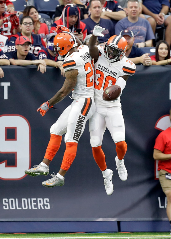 . Cleveland Browns\' Jamar Taylor (21) and Jason McCourty (30) celebrate an interception returned for a touchdown by McCourty on a pass thrown by Houston Texans\' Deshaun Watson in the second half of an NFL football game, Sunday, Oct. 15, 2017, in Houston. (AP Photo/Eric Gay)