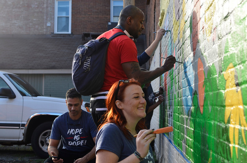 Cameron Ham, above, Kristen Reed, below, and Ken Clowes, left, paint a mural on North Street on the side of Natili North Pizza Shoppe. Butler's addiction recovery group Hope is Dope is painting the mural as part of its art class. Tanner Cole/Butler Eagle