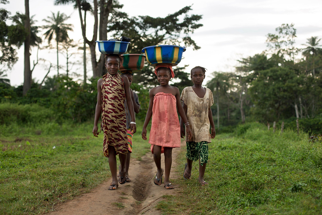 . In this photo taken Sunday Nov. 23, 2014, young girls return from the water well  in the Guinean village of Meliandou, some 400 miles (600 kms) south-east of Conakry, Guinea, believed to be Ebola\'s ground zero. Village chief Amadou Kamano, fearing that the entire village was cursed, said  people from other villages blamed Meliandou for bringing the deaths and, at one point, blocked their access to the only road to the main road and to the water well. (AP Photo/Jerome Delay)