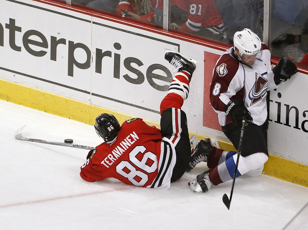. Chicago Blackhawks left wing Teuvo Teravainen (86) and Colorado Avalanche defenseman Jan Hejda collide along the boards during the second period of an NHL hockey game Tuesday, Jan. 6, 2015, in Chicago. (AP Photo/Charles Rex Arbogast)