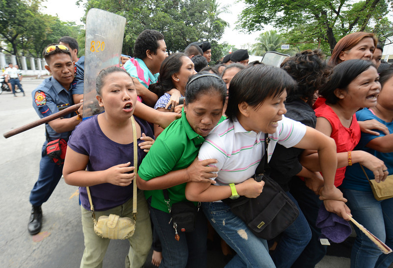 """. Members of Philippine women\'s group Gabriela are pushed back by police during a surprise rally near the gates of Malacanang palace in Manila on March 7, 2013, accusing President Benigno Aquino of mishandling the Sabah stand-off situation between followers of a self-styled Philippine sultan and Malaysian troops. Malaysia\'s defence minister on March 7 rejected a ceasefire offer by a self-styled Philippine sultan unless his fighters who launched a deadly incursion \""""surrender unconditionally\"""".   TED ALJIBE/AFP/Getty Images"""