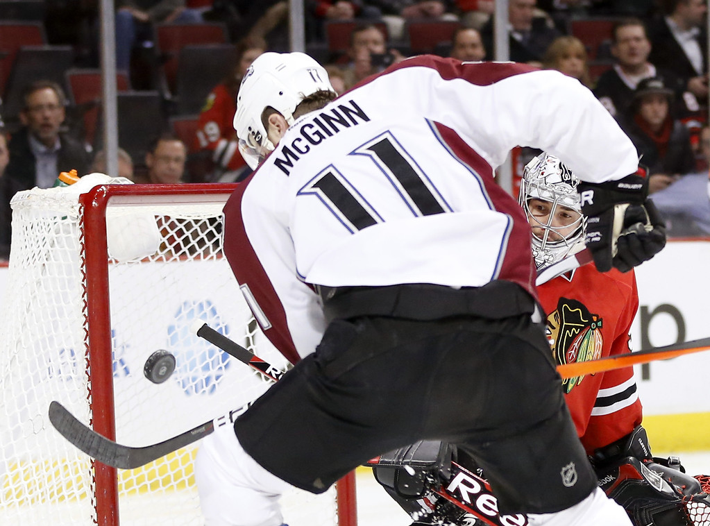. Chicago Blackhawks goalie Corey Crawford, right, keeps an eye on the puck as Colorado Avalanche left wing Jamie McGinn (11) tries to get a rebound shot during the first period of an NHL hockey game Tuesday, March 4, 2014, in Chicago. (AP Photo/Charles Rex Arbogast)