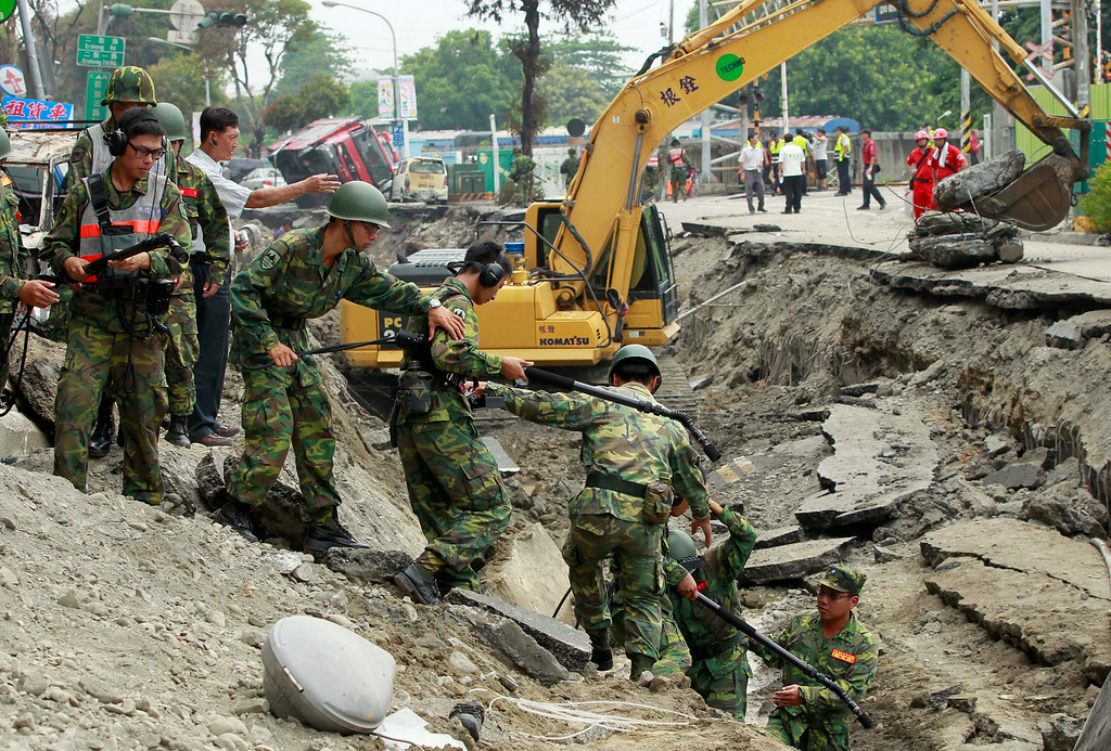 . Soldiers use electronic sensors to search for missing persons believed to be buried after massive gas explosions in Kaohsiung, Taiwan, Friday, Aug. 1, 2014. A series of explosions about midnight Thursday and early Friday ripped through Taiwan\'s second-largest city, killing scores of people, Taiwan\'s National Fire Agency said Friday. (AP Photo/Wally Santana)
