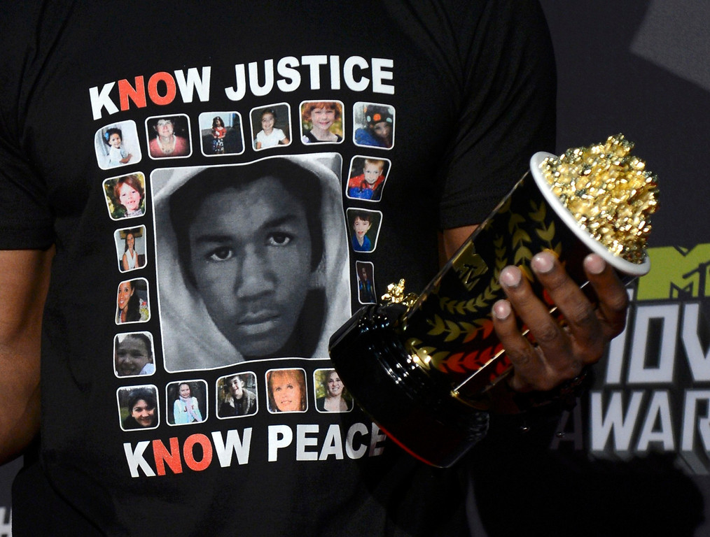 . Detail view of the t-shirt worn by actor Jamie Foxx shows faces of Trayvon Martin and the victims of the Sandy Hook Elementary School shooting as Foxx poses with the MTV generation award backstage at the 2013 MTV Movie Awards in Culver City, California April 14, 2013.   REUTERS/Phil McCarten (