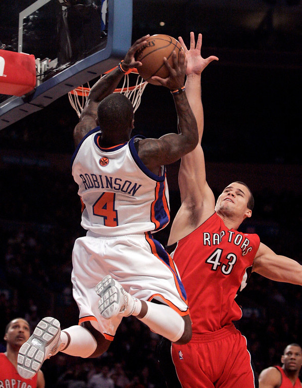 . Toronto Raptors forward Kris Humphries (43) blocks a shot by New York Knicks guard Nate Robinson (4)  during the first half of NBA basketball action Friday, Jan. 11, 2008  in New York.  (AP Photo/Frank Franklin II)