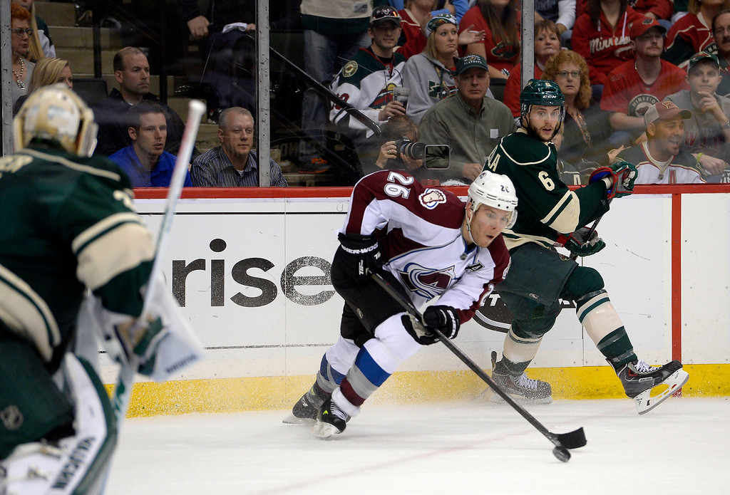 . Colorado Avalanche center Paul Stastny (26) skates the pucks away from Minnesota Wild defenseman Marco Scandella (6) during the second period  April 21, 2014 during round 1 game three of the Stanley Cup Playoffs at Xcel Energy Center. (Photo by John Leyba/The Denver Post)
