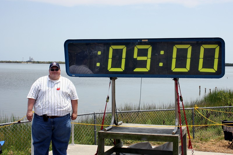Chris with the countdown clock holding at T minus 9 minutes to liftoff, with Space Shuttle Atlantis on Launch Pad 39-A in the background