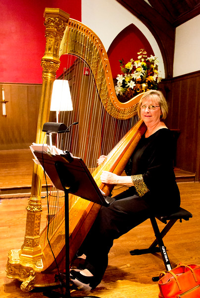 Paula Page posing by her harp