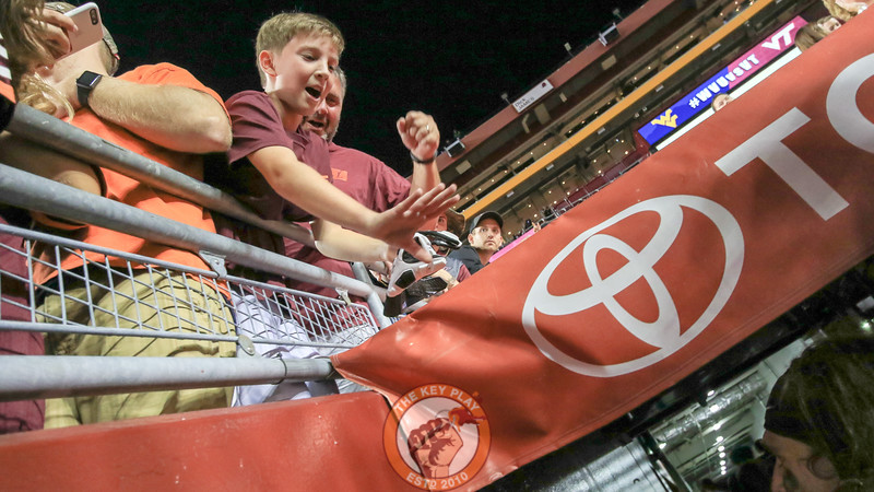 A young Virginia Tech fan waves thanks to Wyatt Teller (far right) after Teller handed him a glove as he walked into the tunnel. Virginia Tech defeated West Virginia 31-24. (Mark Umansky/TheKeyPlay.com)