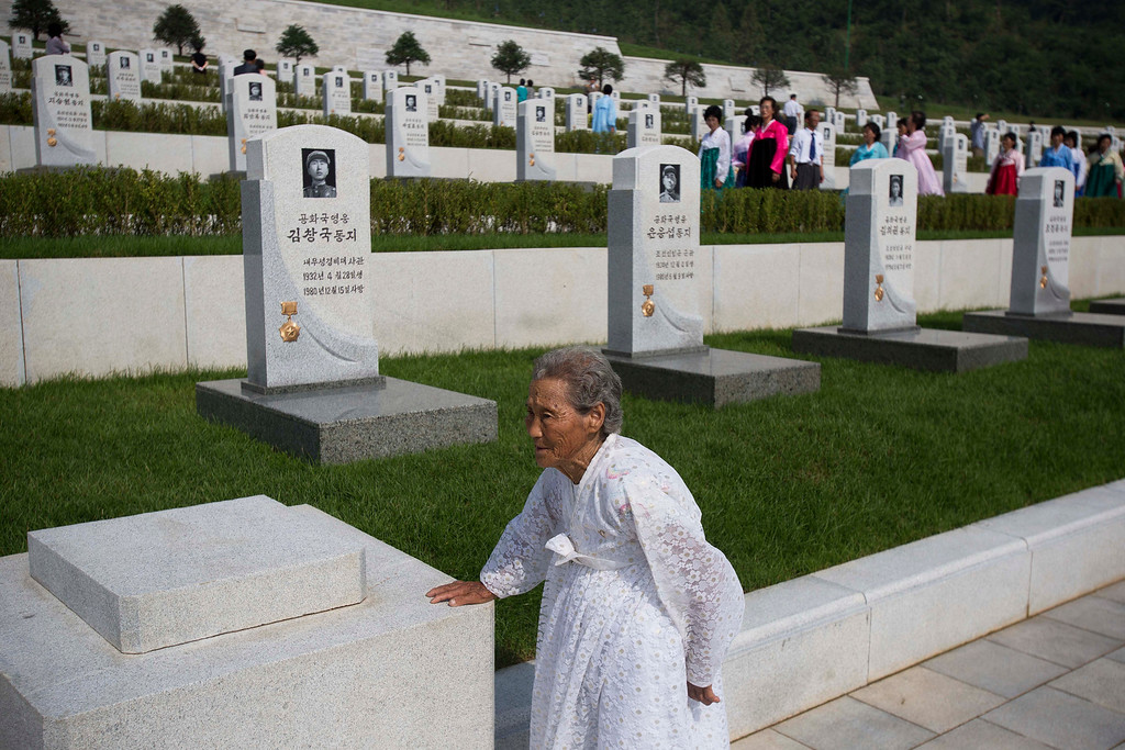 . An elderly North Korean woman stops to rest as she tours a cemetery for Korean War veterans on Thursday, July 25, 2013 in Pyongyang, North Korea during an opening ceremony marking the 60th anniversary of the signing of the armistice that ended hostilities on the Korean peninsula. (AP Photo/David Guttenfelder)