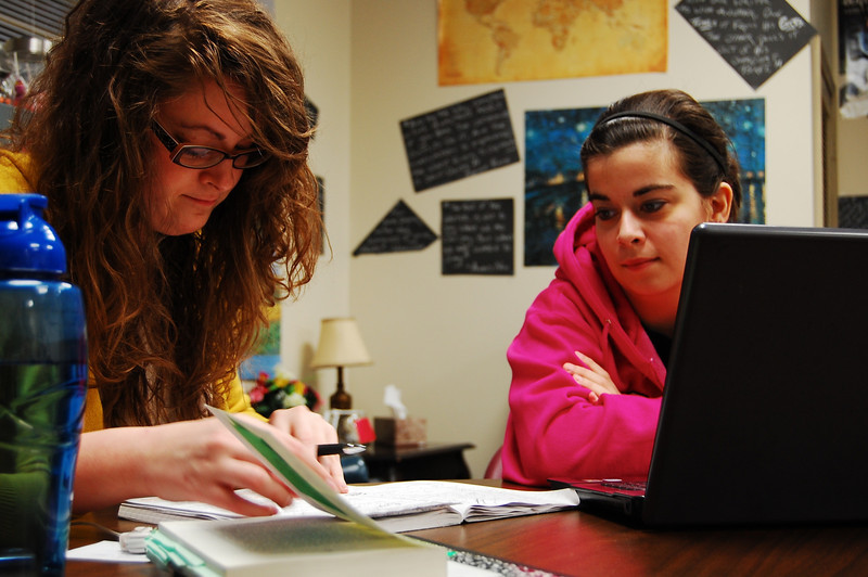 Even with spare time on their hands, Writing Center Employees help each other with homework.