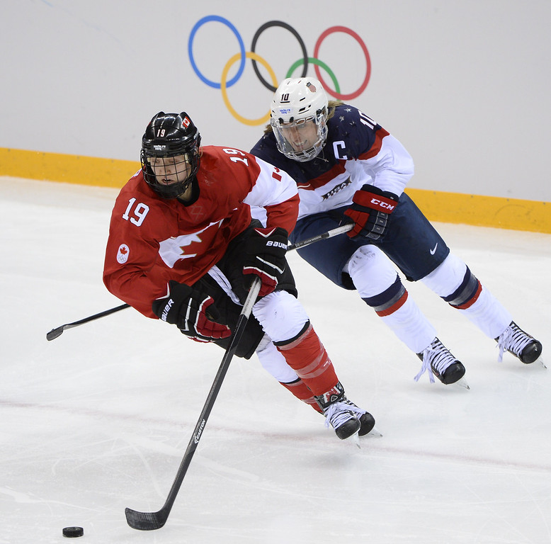 . US Meghan Duggan skates after Canada\'s Brianne Jenner during the Women\'s Ice Hockey Group A match between Canada and USA at the Sochi Winter Olympics on February 12, 2014 at the Shayba Arena. AFP PHOTO / JONATHAN NACKSTRAND/AFP/Getty Images