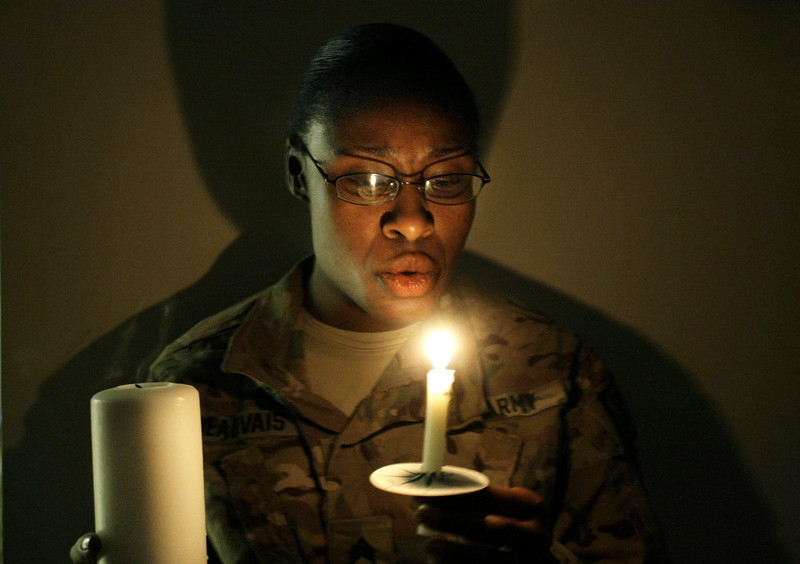 . A U.S. army woman with the NATO- led International Security Assistance Force (ISAF) blows a lit candle on Christmas eve at the U.S.-led coalition base in Kabul, Afghanistan, Monday, Dec. 24, 2014. (AP Photo/Musadeq Sadeq)