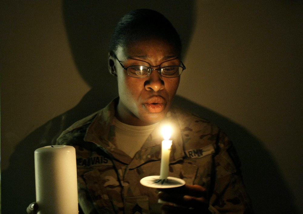 Description of . A U.S. army woman with the NATO- led International Security Assistance Force (ISAF) blows a lit candle on Christmas eve at the U.S.-led coalition base in Kabul, Afghanistan, Monday, Dec. 24, 2014. (AP Photo/Musadeq Sadeq)