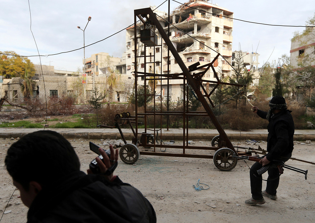 . A Free Syrian Army fighter uses a catapult to fire a homemade grenade at Syrian Army soldiers during a fight in the Arabeen neighborhood of Damascus January 24, 2013.   REUTERS/Goran Tomasevic