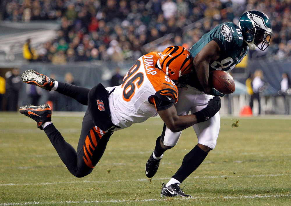 . Philadelphia Eagles receiver Jason Avant is tackled by the Cincinnati Bengals Carlos Dunlap (96) during the second quarter of their NFL football game in Philadelphia, Pennsylvania December 13,  2012. REUTERS/Tim Shaffer