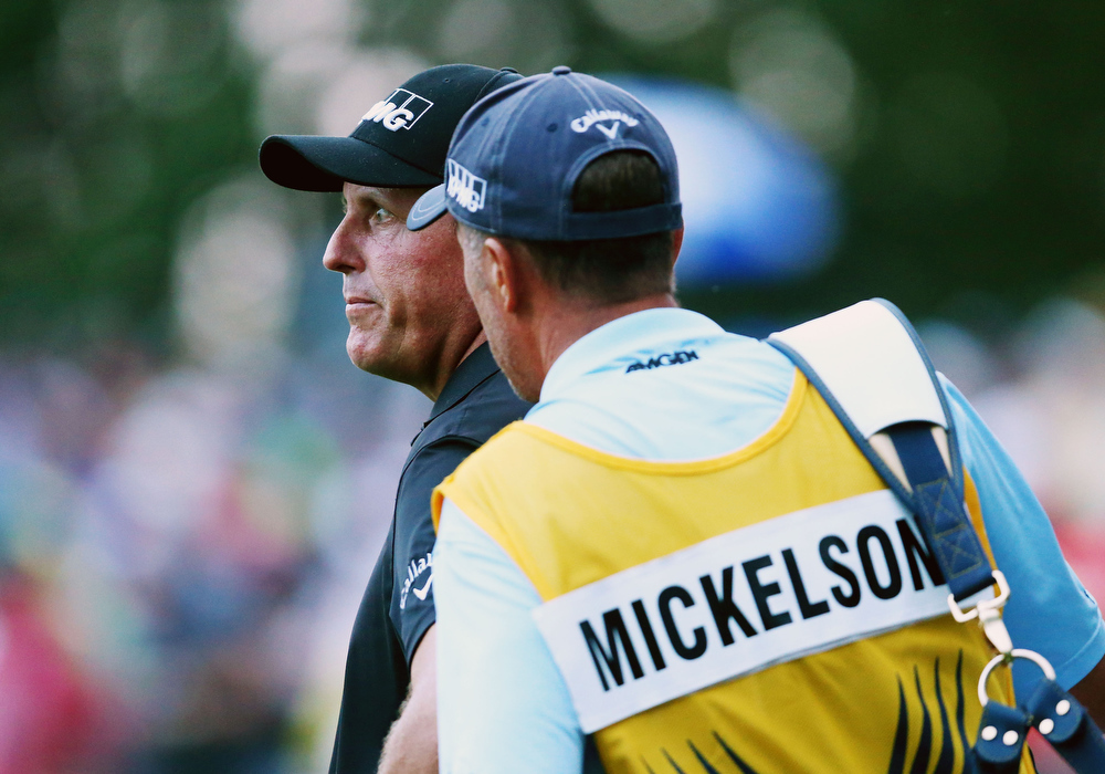 . Phil Mickelson of the United States waits on the 18th green alongside his caddie Jim Mackay during the final round of the 96th PGA Championship at Valhalla Golf Club on August 10, 2014 in Louisville, Kentucky.  (Photo by Jeff Gross/Getty Images)