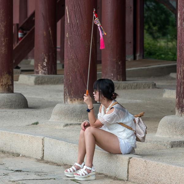 Woman sitting at ledge, Geunjeongjeon Building, Gyeongbokgung Palace, Seoul, South Korea