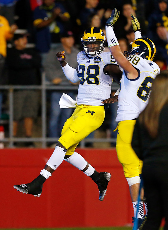. Michigan quarterback Devin Gardner (98) celebrates with Jake Butt (88) after running for a touchdown during the second half of an NCAA college football game against Rutgers on Saturday, Oct. 4, 2014, in Piscataway, N.J. Rutgers defeated Michigan 26-24. (AP Photo/Rich Schultz)