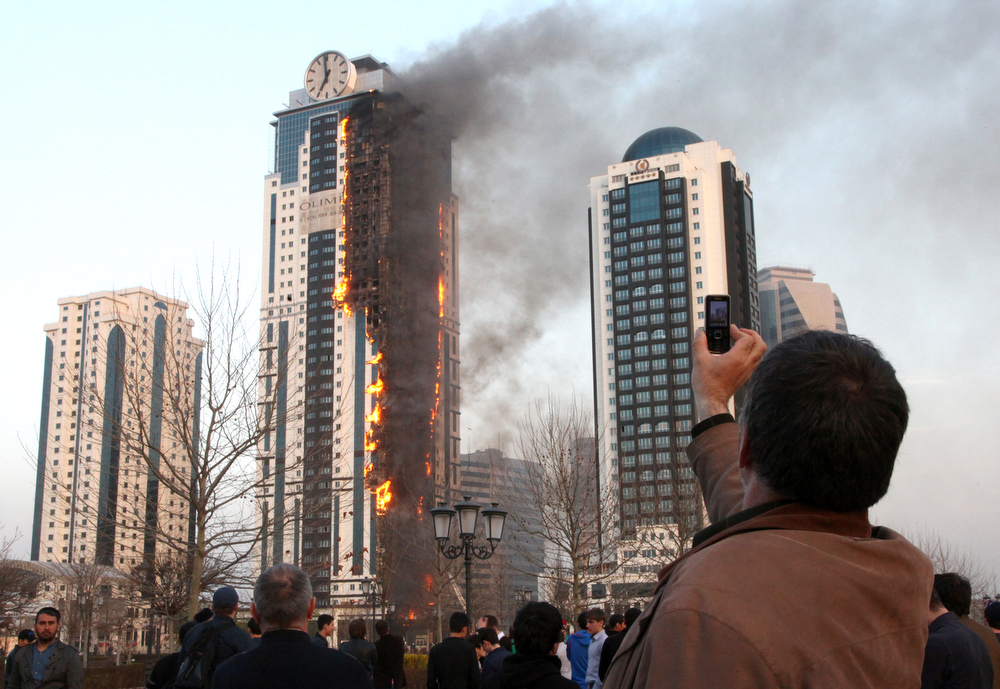 . A man takes a picture of a burning skyscraper  in central Grozny on April 3, 2013. A fire raged in a skyscraper in the Chechnya capital Grozny on Wednesday, a building which is a centrepiece of a drive by local authorities to promote the city as a glitzy and modern hub.The buildng is uninhabited.  ELENA FITKULINA/AFP/Getty Images