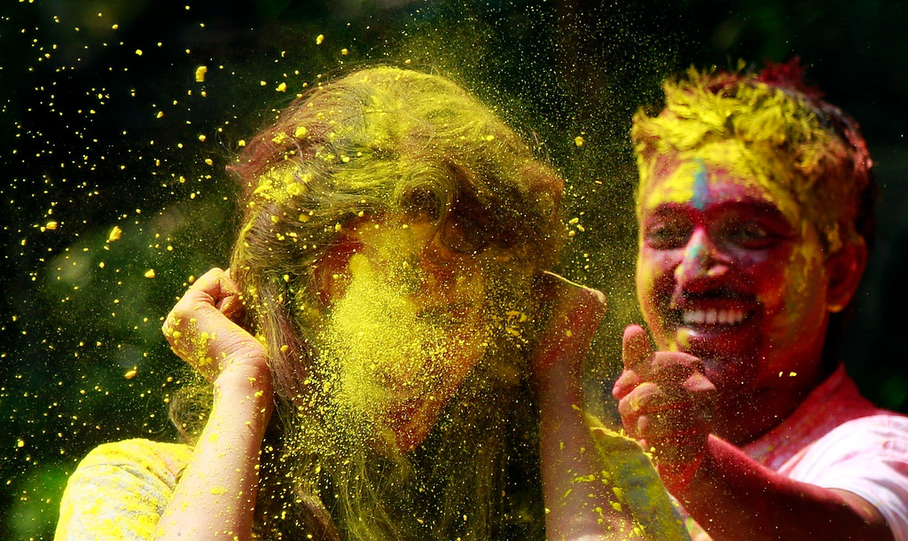 . An Indian man throws colored powder on a woman as they celebrate Holi, the Hindu festival of colors, in Mumbai India, Monday, March 17, 2014. The festival heralds the arrival of spring. (AP Photo/ Rafiq Maqbool)