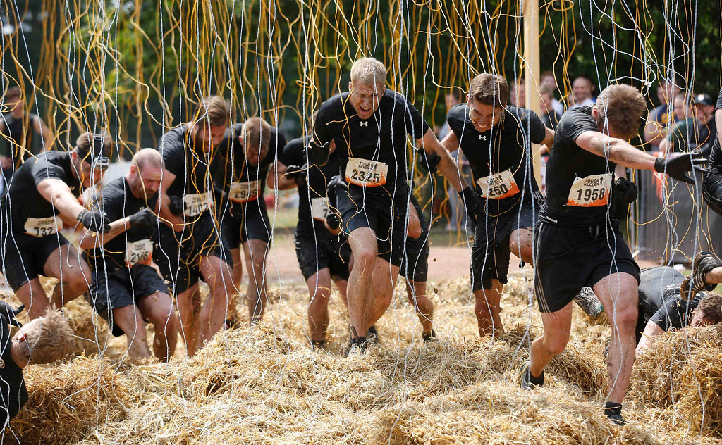 """. Participants of the \""""Tough Mudder\"""" endurance event series run through the \""""Electroshock Therapy\"""" obstacle made of electrical wire holding some 10,000 Volts in the Fursten Forest, a former British Army training ground near the north-western German city of Osnabrueck July 13, 2013. The hardcore but un-timed event over 16 km (10 miles) was designed by British Special Forces to test mental as well as physical strength. Some 4,000 competitors had to overcome obstacles of common human fears, such as fire, water, electricity and heights.   REUTERS/Wolfgang Rattay"""