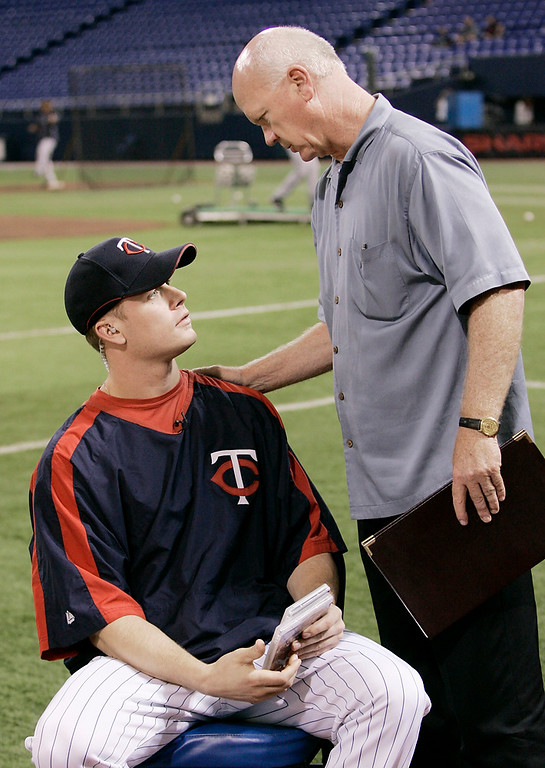 . Twins general manager Terry Ryan, right, visits with the injured Justin Morneau who was on hand for a pre-game interview before the Twins-Toronto Blue Jays game Tuesday, June 26, 2007, in Minneapolis. Morneau received a bruised right lung in a collision a week earlier. (AP Photo/Jim Mone)